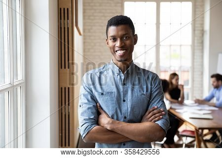 Millennial African Staff Member With Arms Crossed Posing In Office
