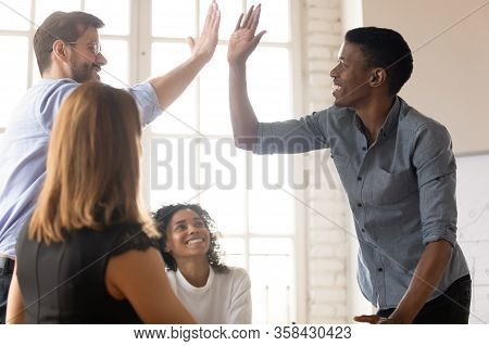 African And Caucasian Buddies Giving High Five Greeting Each Other