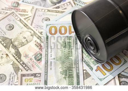 Barrel Of Oil On A Background, American Dollars Background. Falling Trend Of Barrel Price Decrease O