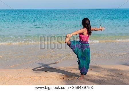 Asian Thai Woman Practicing Yoga In Ao Thong Nai Pan Noi Beach, Koh Phangan Island, Thailand