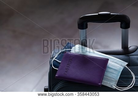 Travel Suitcase, Passport And Medical Mask. The Ban On Travel During The Epidemic Of The Coronavirus