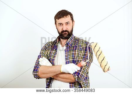 Confident Painter Worker Man. Bearded Man With Paint Roller Over White Wall. Home Renovation Concept