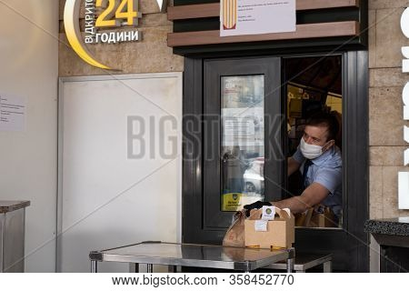 Kiev, Ukraine, 27 March 2020, Man In Facial Protective Mask Gives Fastfood Hamburgers Thru Window At