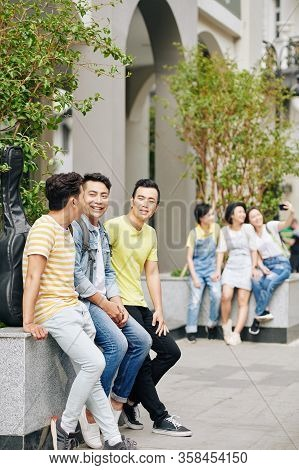 Cheerful Students Resting Outdoors After Classes In University And Discussing Homework And Plans For
