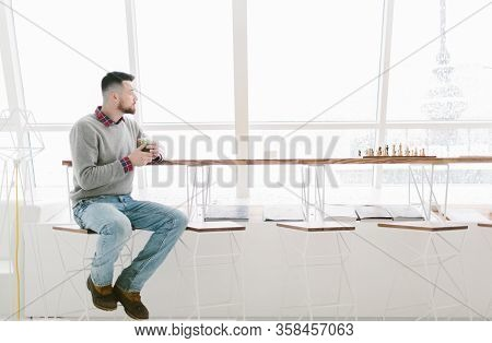 Young Bearded Man In Cafe. Sits On High Chair At Long Desk Near Window. Man Holds Glass With Green D