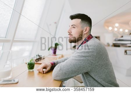 Young Bearded Man In Cafe. He Sits At Long Table Near Window. Beverage With Green Leaves Smartphone
