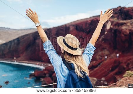 Tourist Looking At Red Beach Landscape From View Point In Akrotiri Santorini Greece. Happy Woman Tra