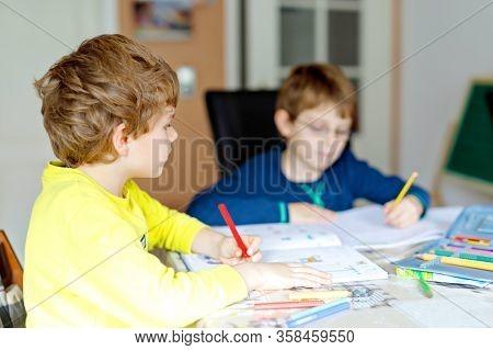 Two Hard-working School Kids Boys Making Homework During Quarantine Time From Corona Pandemic Diseas