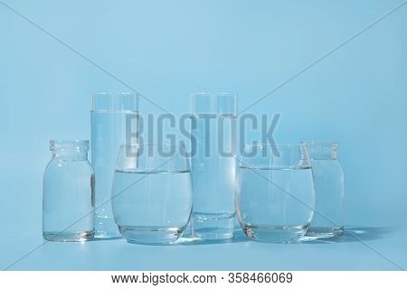 Glasses With Clean Water In Different Shapes On Blue. Concept Of Benefits Of Clean And Fresh Water.
