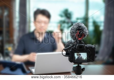 Online Lecture Concept. Asian Middle-aged Man Giving Online Lectures At Home.