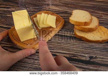 Wooden Butter Dish With A Piece Of Butter And Slices Of Cheese And Fresh Wheat Toast On A Wooden Bac