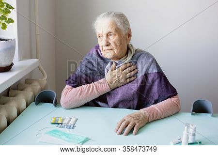 Sad Elderly Caucasian Woman Quarantined During  Virus Outbreak. She Sitting By Window, On Table Pill