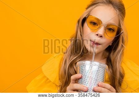 Portrait Of Young Caucaian Girl With Long Fair Hair In Yellow Glasses Drinks A Juice And Smiles