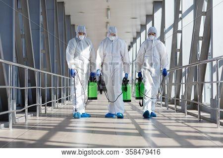 People In Protective Hazmat Suits Carrying Barrels, Pathogen Respiratory Quarantine Coronavirus Conc