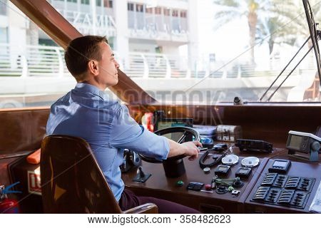 A Man Drives A Sea Pleasure Boat. A Male Captain Of A Watercraft Boat At The Helm Of A Boat.