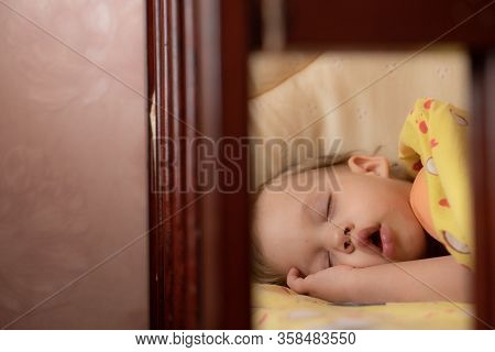 A Little Boy, 2 Years Old, Sleeps Alone In A Cot. The Baby Sleeps In The Cradle With His Hand Under