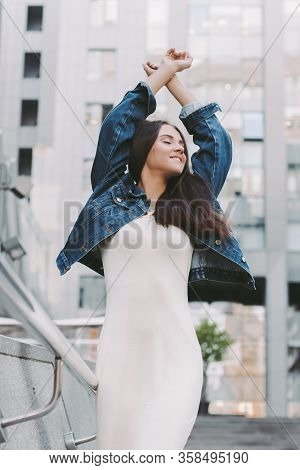 Carefree Happy Beautiful Young Woman In Stylish Denim Jacket Dancing And Having Fun Outdoors. Attrac