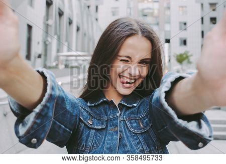 Young Positive Stylish Hipster Girl Winking And Showing Tongue While Making Selfie On Camera. Cheerf
