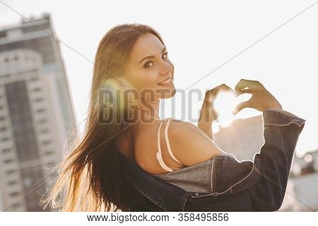 Young Happy Woman Showing Heart Shape With Hands While Walking City Street. Beautiful Fashionable Hi