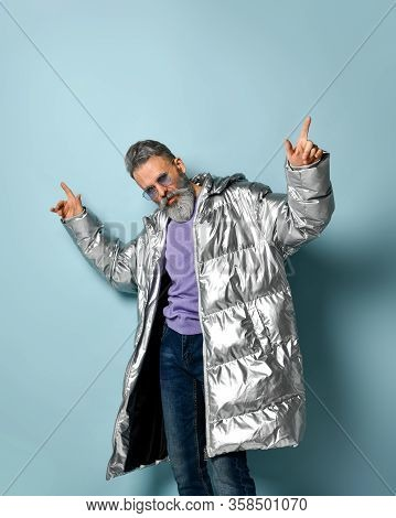 Gray-haired, Bearded Aged Male In Purple Pullover And Sunglasses, Silver Colored Down Puffy Jacket,
