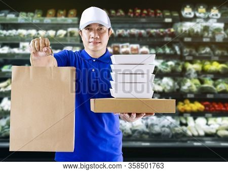 Food Delivery Service Or Shopping Order Online. Delivery Man In Blue Uniform His Hand Holding Paper