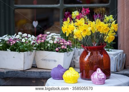 Easter Still Life Composition With Bunnies Figurines And Yellow Flowers Of Narcissus In Glass Vase