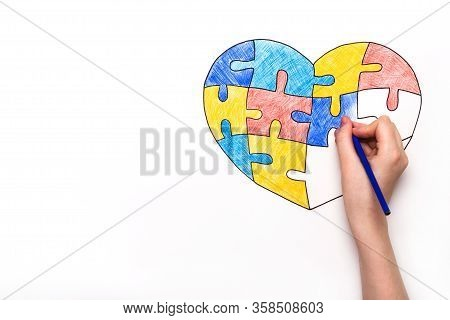 World Autism Awareness Day. Childrens Hand Draws Heart From Multi-colored Puzzles. Mental Health Car