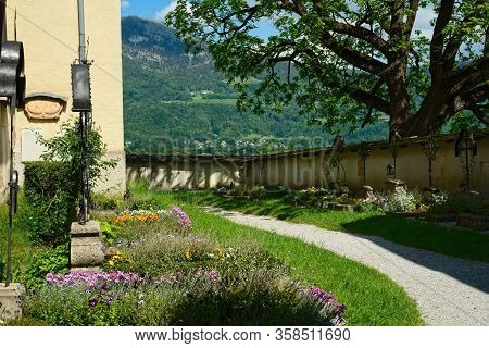 Old Graves In The Nonnberg Abbey Courtyard In Salzburg, Austria; The Nearby Gaisberg Looms Over The