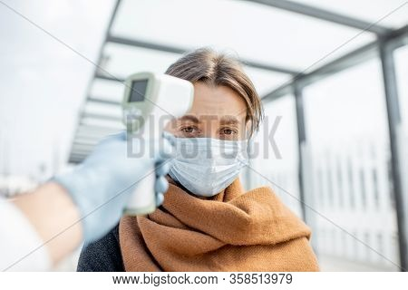Measuring Temperature With Infrared Thermometer Of A Young Woman In Face Mask At A Checkpoint During