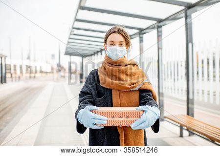 Young Woman In Medical Mask And Gloves Holding Cardboard With Pizzas Going Out For Food During The E
