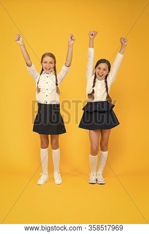 Celebrating Back To School. Happy Girls Celebrating Achievement In Study On Yellow Background. Small
