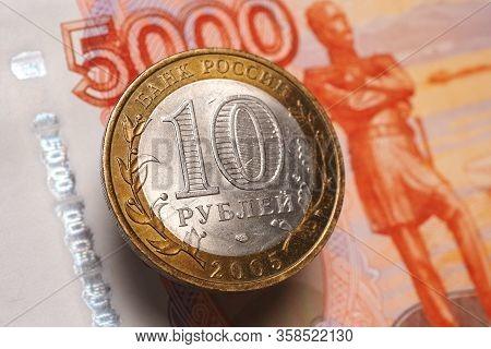 Russian Bimetallic 10 Ten Ruble Coin Hangs In The Air Above A 5000 Five Thousand Ruble Banknote