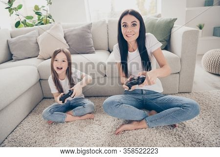 Full Length Photo Of Excited Energetic Mommy Small Kid Sit Legs Crossed Carpet Play Video Game Want