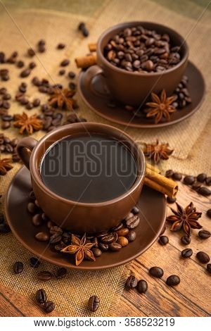 Coffee In Dark Brown Cups And Saucers On Napkins On A Wooden Table With Spilled Coffee Beans, Star A