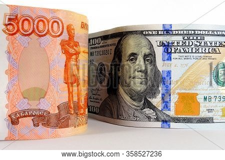 A Russian Banknote Of 5000 Rubles And An American Banknote Of 100 Dollars Are Standing Next To A Lig