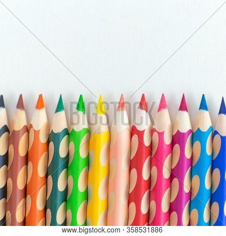 Color Pencils On A White Background With Copy Space. Ergonomic Triangular Colored Pencil With Non-sl
