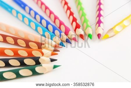 Color pencils  lie in a semicircle on a white background with copy space. Selected focus.  Ergonomic
