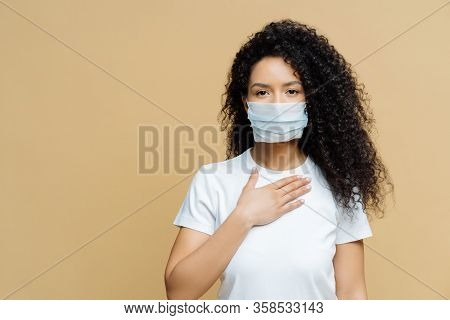 Serious Afro American Woman Wears Medical Face Mask, Has Problems With Breathing, Presses Hand To Ch