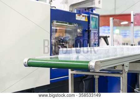 Many Row Of Clear Plastic Cup Or Box After Made By Plastic Injection Mold Machine On Automatic Conve