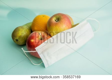 Fruit And Protective Mask On A Mint Background, Fruit Harvest, Protection From Coronavirus, Fruit Fr