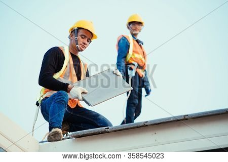 Engineer Wear Safety Uniform Inspection Installing New Roof Of Modern House.