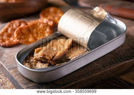 A Can Of Smoked Kippers And Crackers On A Rustic Wood Table Top.