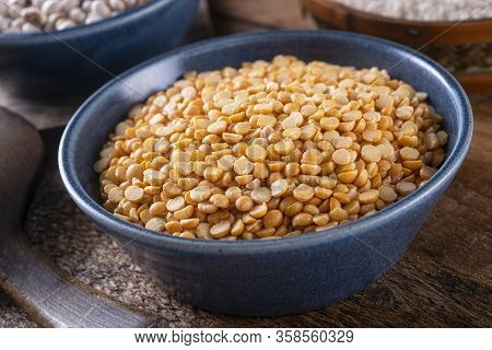 A Bowl Of Dried Split Yellow Peas On A Rustic Wood Table Top.