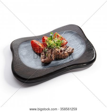 Grilled marbled beef with tomatoes side view. Roasted meat with cut vegetables and garden cress. Tasty dish served with greenery and sauce on wooden surface. Haute cuisine, restaurant food