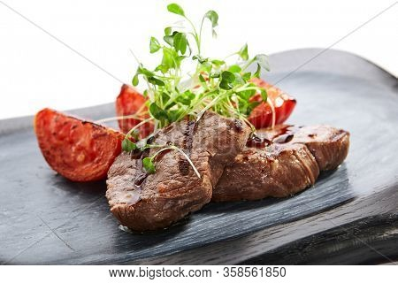 Grilled marbled beef with tomatoes top view. Roasted meat with cut vegetables and garden cress. Tasty dish served with greenery and sauce on wooden surface. Haute cuisine, restaurant food