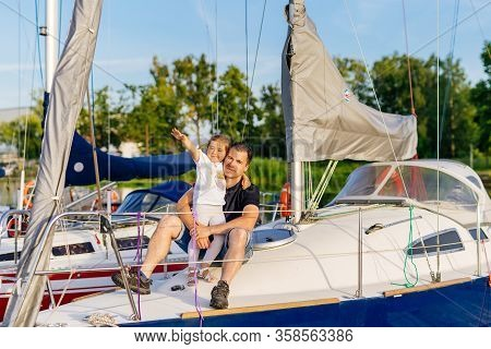 Portrait Of Smiling Father And Daughter On Prow Of Sailboat Or Yacht Anchored In Marina At Bright Su
