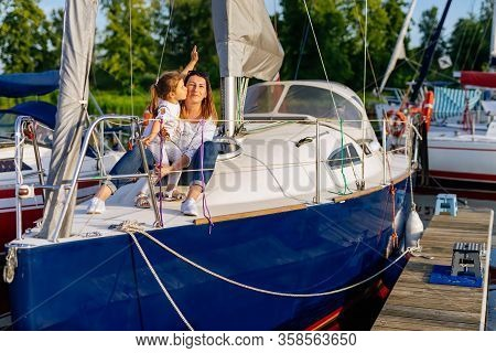 Portrait Of Smiling Mother And Daughter On Prow Of Sailboat Or Yacht Anchored In Marina At Bright Su