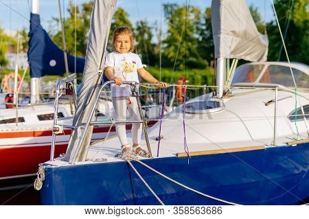 Portrait Of Young Caucasian White Girl On Prow Of Sailboat Or Yacht Anchored In Marina At Bright Sun