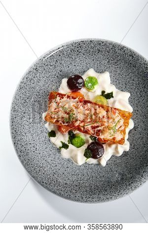 Crab and creamy cheese. Delicious chopped seafood and greenery on plate. Prepared dish with sauce. Tasty restaurant delicacy. Culinary composition, food presentation. Haute cuisine