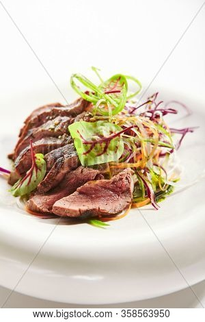 Tataki roast beef closeup view. Tasty grilled meat with onion and greenery. National cuisine, traditional asian recipe. Japanese culinary method. Delicious meal with sauce and seasonings